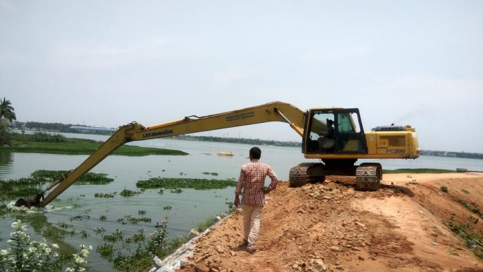 Water in Lakshmisagar Lake at Narasapura in Kolar taluk has already turned green. An excavator removes hyacinth from the water on Friday. dh photo/chiranjeevi kulkarni