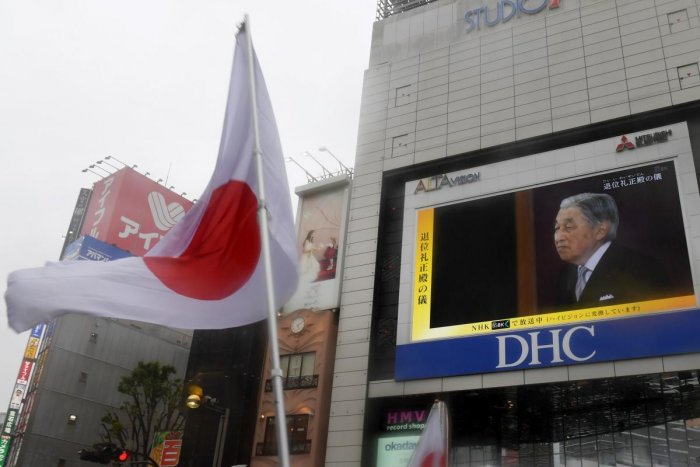 The Japan national flag is seen during a live broadcast of Japan's Emperor Akihito's abdication ceremony on a screen in Tokyo on April 30, 2019. AFP