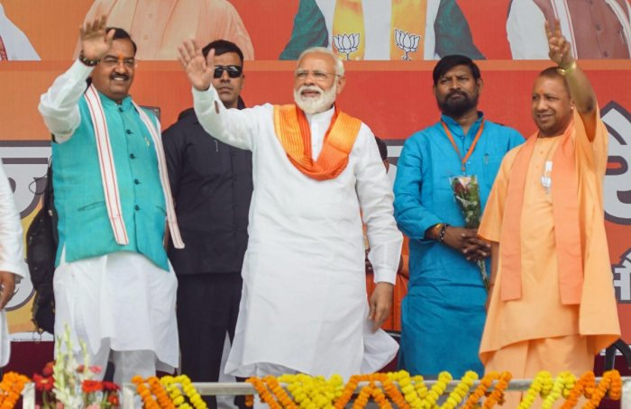 Bhadohi: Prime Minister Narendra Modi with UP Chief Minister Yogi Adityanath and Dy CM Keshav Prasad Maurya waves at the crowd during an election campaign rally for the Lok Sabha polls, in Bhadohi, Sunday, May 5, 2019. (PTI Photo)