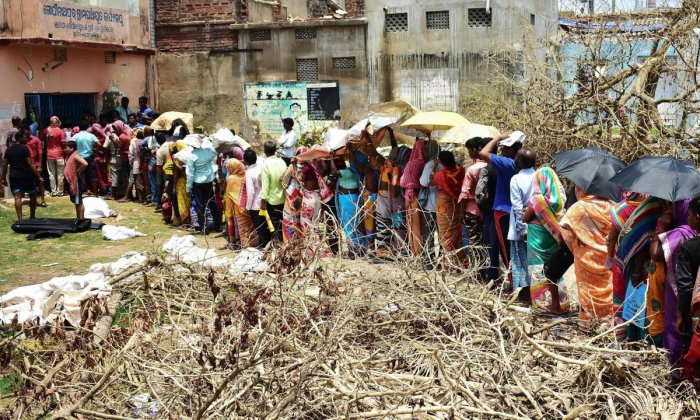 Residents queue to collect relief materials in Puri. (AFP Photo)