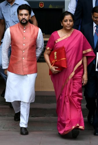 Indian Finance Minister Nirmala Sitharaman (R) with Minister of State for Finance Anurag Thakur (L) leave the Indian Finance Ministry for Parliament House to table the General Budget 2019-20 in New Delhi on July 5, 2019. (Photo by Money SHARMA / AFP)