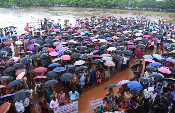 Teachers hold umbrellas to protect themselves from rain during a protest staged at Nehru Maidan in Mangaluru on Tuesday.
