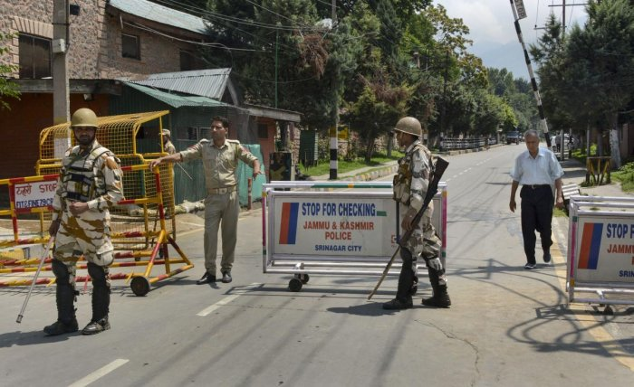 Security personnel stand guard as they block a road leading to the residence of Farooq Abdullah, Omar Abdullah and Mehbooba Mufti during restrictions in Srinagar. (PTI Photo)