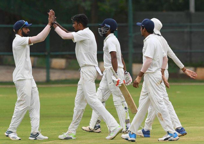 India Green's Ishan Porel (second from left) celebrates with skipper Faiz Fazal after dismissing India Blue's Jalaj Saxena at the Just Cricket ground. DH PHOTO/ SRIKANTA SHARMA R