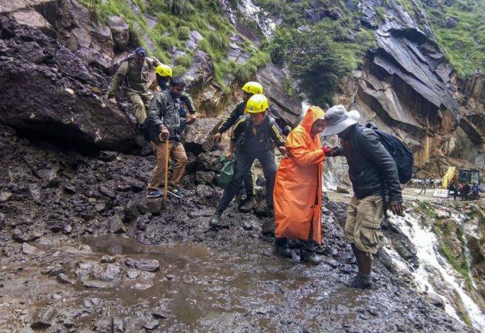 State Disaster Response Force (SDRF) team helps pilgrims cross damaged path on the route of Kailash Mansarovar Yatra, in Pithoragarh district (PTI Photo)