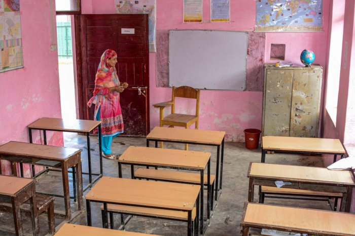 A government school employee inspects a classroom in Srinagar, Monday, Aug. 19, 2019. Teachers and staffs reportedly showed up in most of the schools but students didn't as parents were apprehensive about the security situation in view of violent protests