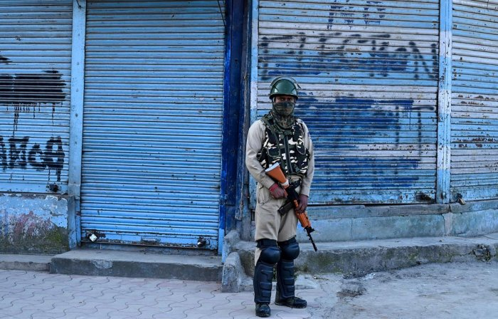 A security personnel stands guard in front of closed shops in Srinagar. AFP file photo