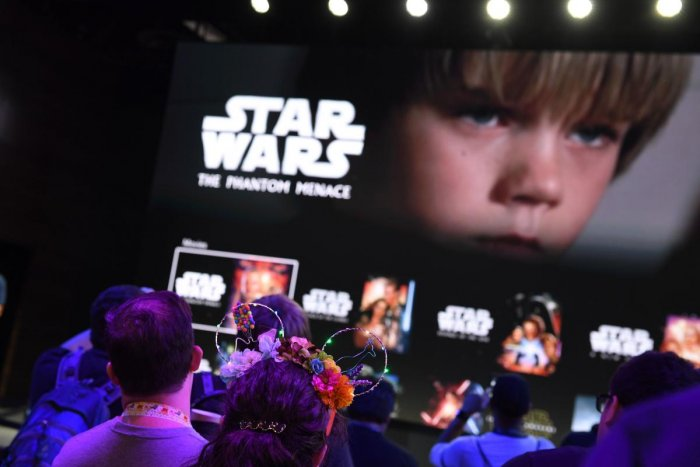 """Attendees get a preview of the Disney+ streaming service interface at the D23 Expo, billed as the """"largest Disney fan event in the world,"""" August 23, 2019 at the Anaheim Convention Center in Anaheim, California. (Photo by AFP)"""