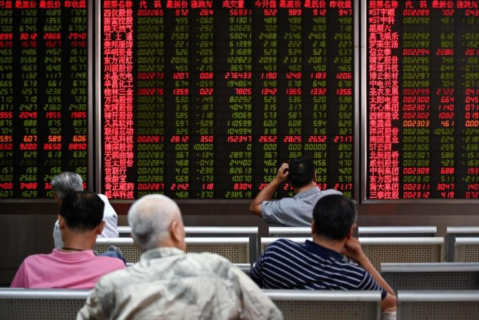 Investors rest on a chair in front of screens showing stock market movements at a securities company in Beijing. (AFP Photo)