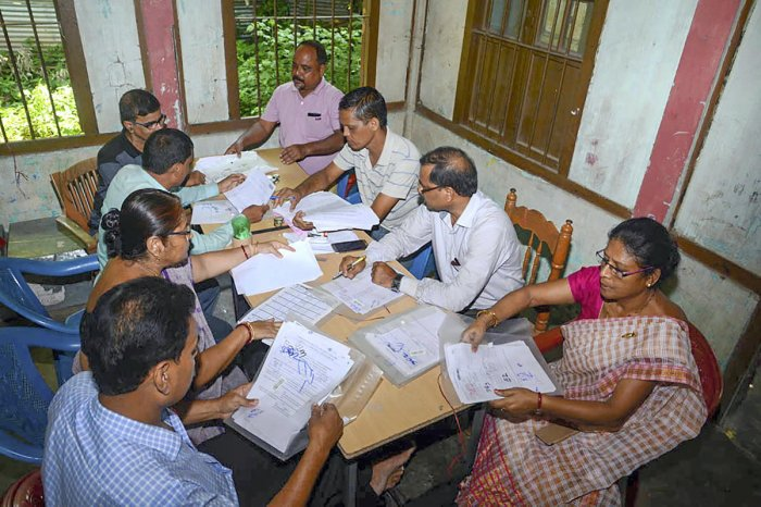 Officials check the documents submitted by people, ahead of the release of the final draft of National Register of Citizens (NRC), at an NRC Seva Kendra in Guwahati. PTI file photo