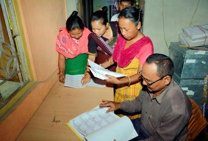 Bodo women check their names in the final list of National Register of Citizens (NRC), at an NRC Seva Kendra at Bagan Para in Baska district of Assam, Monday, Sept 2, 2019. PTI