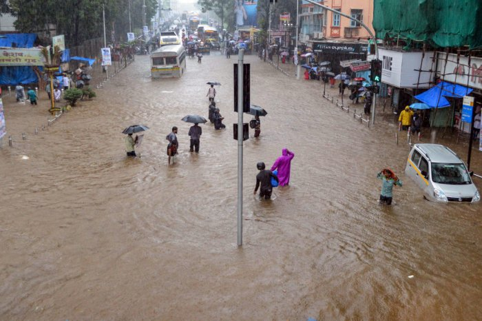 Residents wade through a flooded street, following heavy rains in the low lying area of Dadar, in Mumbai. PTI File Photo