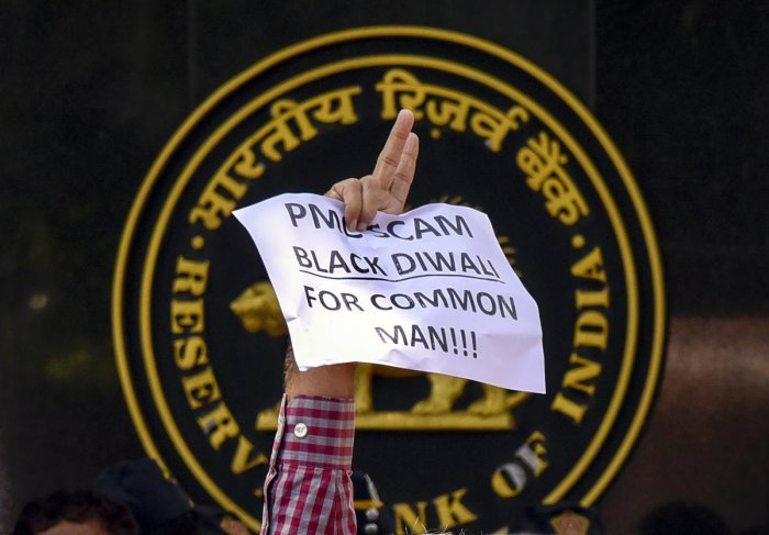 A depositor of Punjab and Maharashtra Cooperative (PMC) bank displays a placard during a protest over the bank's crisis, outside the Reserve Bank of India building, in Mumbai. (PTI Photo)