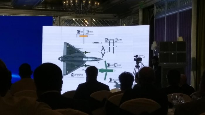 Delegates at the Synergia Conclave look at an image of drones.