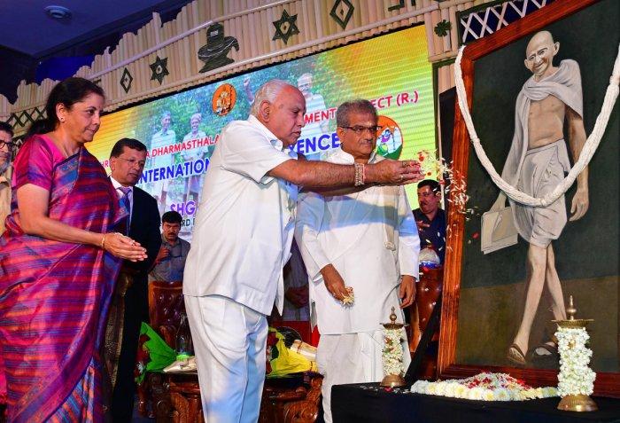 Chief Minister B S Yediyurappa inaugurates a conference organised by the Shri Kshetra Dharmasthala Rural Development Project on Wednesday. Finance Minister Nirmala Sitharaman and Dharmadhikari of Dharmastala, Veerendra Heggade, are seen. DH photo/Krishnak