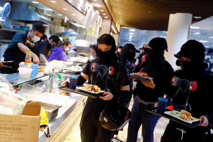 Protesters hold food trays at the Polytechnic University in Hong Kong, China November 14, 2019. REUTERS/Thomas Peter