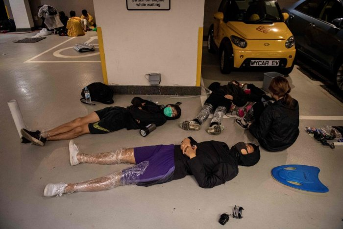 Protesters sleep on the floor of a parking lot inside the Hong Kong Polytechnic University in the Hung Hom district of Hong Kong. (Photo by Reuters)