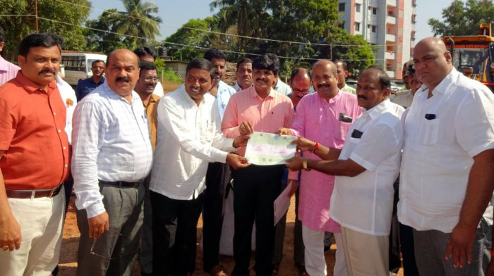 Deputy Commissioner G Jagadeesha hands over trip sheet to a lorry owner who had registered online for sand transportation at Hiriyadka sand stockyard in Udupi.