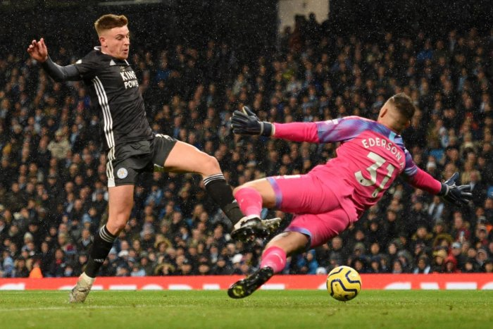 Leicester City's English midfielder Harvey Barnes tries to reach a cross as Manchester City's Brazilian goalkeeper Ederson (R) tries to block during the English Premier League football match between Manchester City and Leicester City at the Etihad Stadium