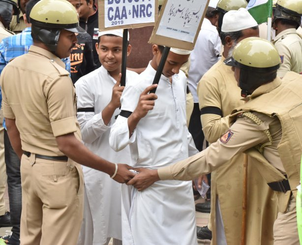 Policemen frisk young boys participating in the rally on Monday. DH PHOTO/JANARDHAN B K