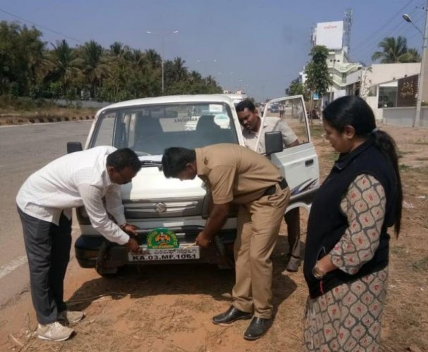 Transport department officials, led by Mysuru (East) RTO K S Soundarya, remove a defective number plate from a vehicle, in Mysuru. pic by special arrangement