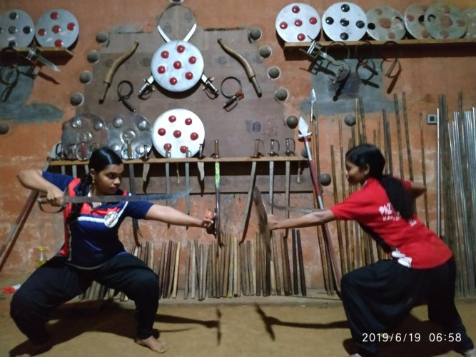 Anushree and Archa wield a sword and a shield in a combat exercise.
