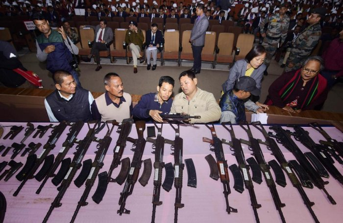 Security personnel arrange the arms and ammunitions to be put on display during the arms laying down ceremony at GMCH auditorium, in Guwahati, Thursday, Jan. 23, 2020. A total of 644 militants of eight banned insurgent outfits surrendered in Assam today along with 177 arms. (PTI Photo)