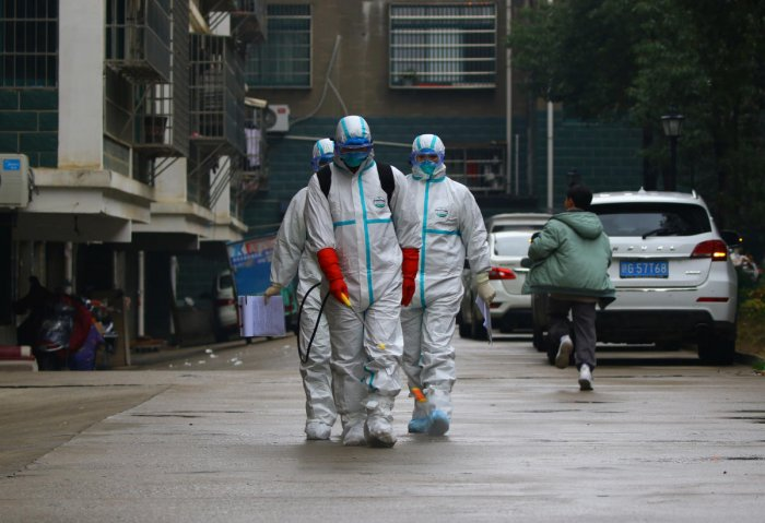 Workers from local disease control and prevention department in protective suits disinfect a residential area following the outbreak of a new coronavirus, in Ruichang, Jiangxi province, China January 25, 2020. (Reuters Photo)