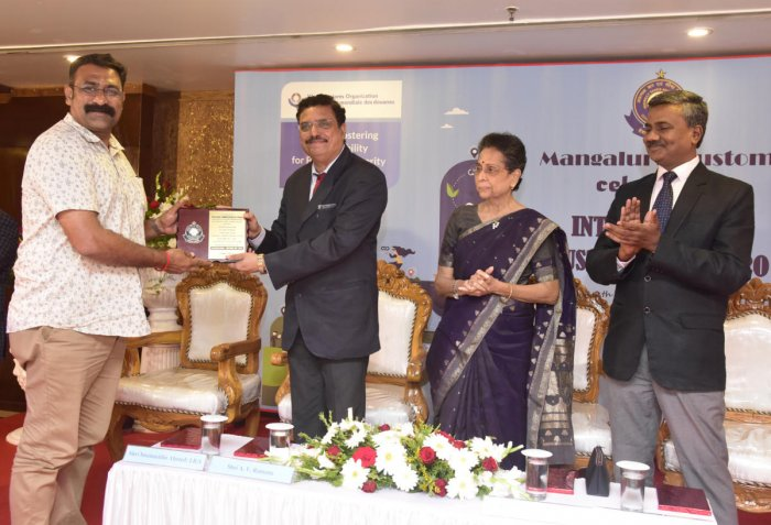 A member of the Anti Rowdy Squad receives a certificate of commendation from New Mangalore Port Trust ChairmanA V Ramana during the International Customs Day programme organised at Hotel Ocean Pearl in Mangaluru on Tuesday.