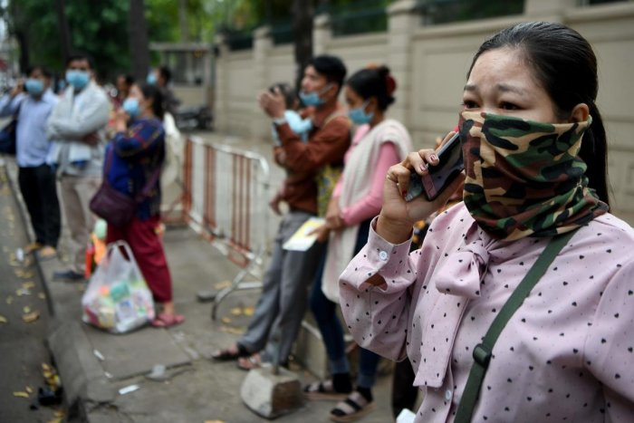 People wear face masks as they stand in front of a children's hospital in Phnom Penh on January 30, 2020, after the first case of novel coronavirus was reported in the country. (AFP Photo)