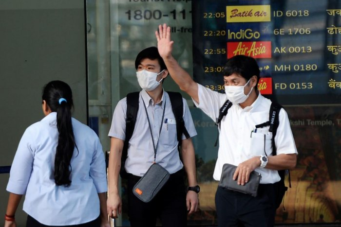 Travellers wearing face masks as prevention for the SARS-like virus outbreak which began in the Chinese city of Wuhan, stand outside Anna International airport in Chennai on January 31, 2020. (AFP Photo)