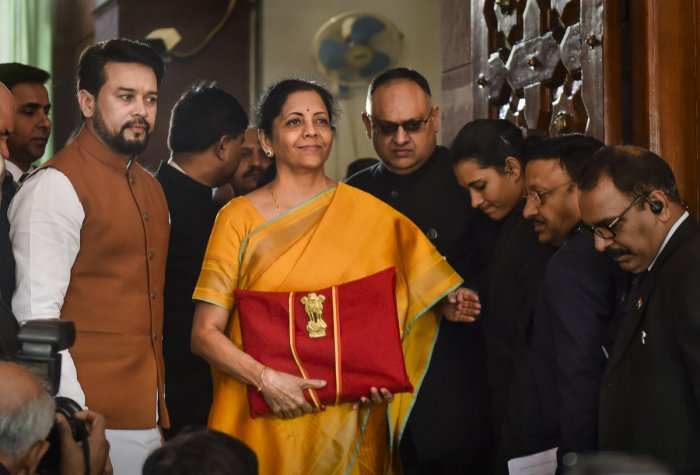 Union Finance Minister Nirmala Sitharaman, flanked by her deputy Anurag Thakur (to her right) and a team of officials, shows a folder containing the Union Budget documents as she poses for lensmen on her arrival at Parliament in New Delhi, Saturday, Feb. 1, 2020. (PTI Photo)
