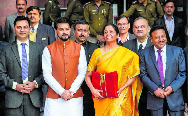 Union Finance Minister Nirmala Sitharaman, holding a folder containing the Union Budget documents, poses for photographers along with her deputy Anurag Thakur and a team of officials, outside the Ministry of Finance, North Block in New Delhi, Saturday, Feb. 1, 2020. (PTI Photo/Kamal Singh)