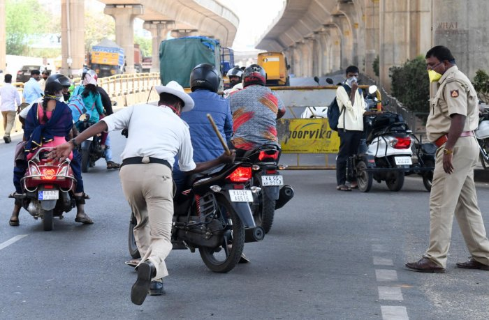 A traffic policeman canes a motorcyclist at T Dasarahalli on Tuesday. (R) This is how a cop caught hold of a man who stepped out on Mysuru Road. DH PhotoS/ B H Shivakumar AND ANUP RAGH T