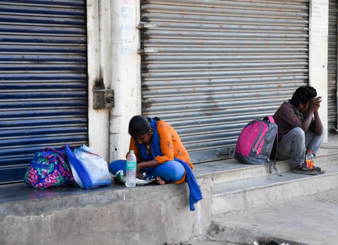 A Family taking rest, who walking to reach their place, at Madavara, during a nationwide lockdown, imposed in the wake of coronavirus pandemic, Outskirts of Bengaluru on Tuesday. Photo/ BH Shivakumar