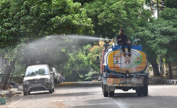 A worker sprays disinfectant on a road at Sanjaynagar in Bengaluru on Tuesday. DH Photo/Janardhan B K