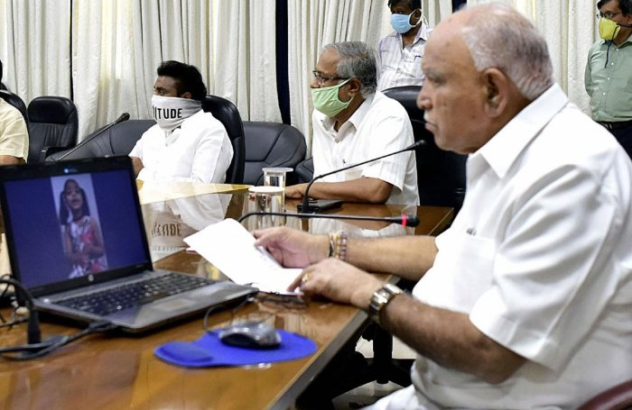 Karnataka Chief Minister B S Yediyurappa (R) with State Education Minister Suresh Kumar (C) inaugurates Youtube Children's Helpline for primary school children, as the nationwide COVID-19 lockdown continues, in Bengaluru, Thursday, Thursday, April 16, 2020. (PTI Photo)