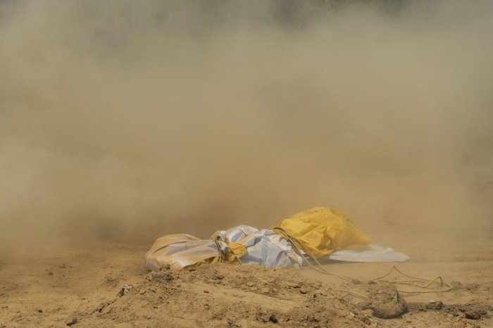 Dust covers the dead body of a woman, who died from the COVID-19 coronavirus disease, before her burial at a graveyard in New Delhi on April 16, 2020. (Photo by SAJJAD HUSSAIN / AFP)
