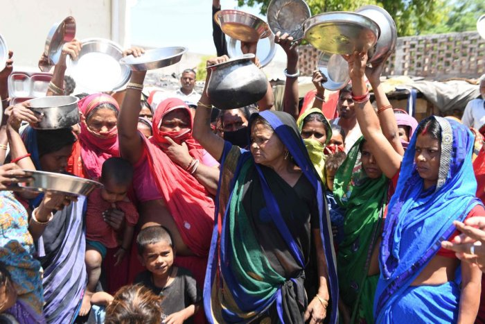 Migrant labourers and families from Bihar and Uttar Pradesh states hold kitchen utensils as they protest against the government for the lack of food at a slum area during a government-imposed nationwide lockdown as a preventive measure against the COVID-1