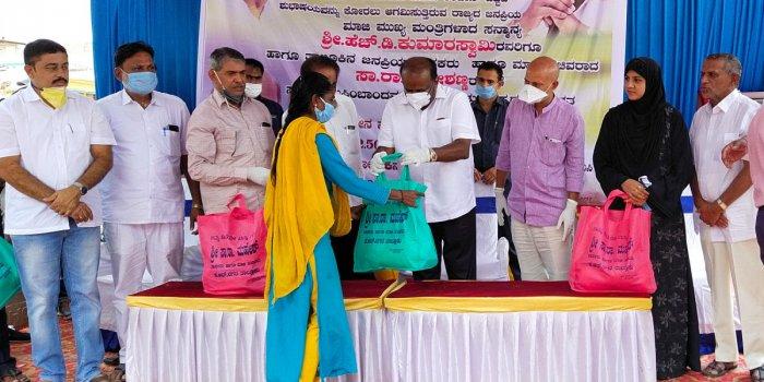 Former chief minister H D Kumaraswamy distribute food kits to the resident of Muslim Layout in K R Nagar, Mysuru district, on Sunday. MLA Sa Ra Mahesh is seen.