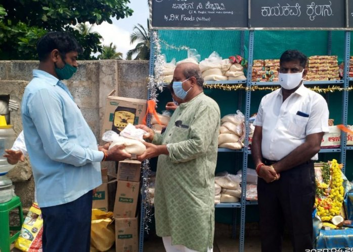 MLA Raghupathi Bhat distributes essential commodities from the wall of humanity in Udupi.