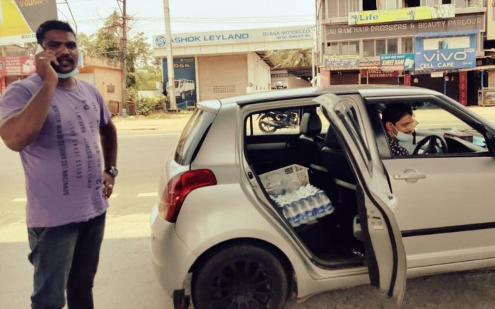 Samad from Ullal and Yasir Angaragundi from Baikampady (seated inside the car) distribute packaged mineral water to thirsty people.