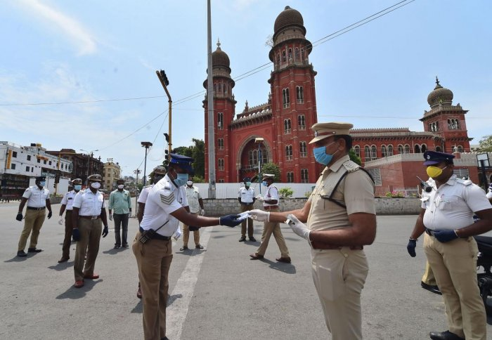 Assistant Commissioner of Police (ACP), Traffic, Ravichandran distributes vitamin tablets to his colleagues in a bid to improve immunity against COVID-19 outbreak during the nationwide lockdown, in Chennai. (PTI Photo)