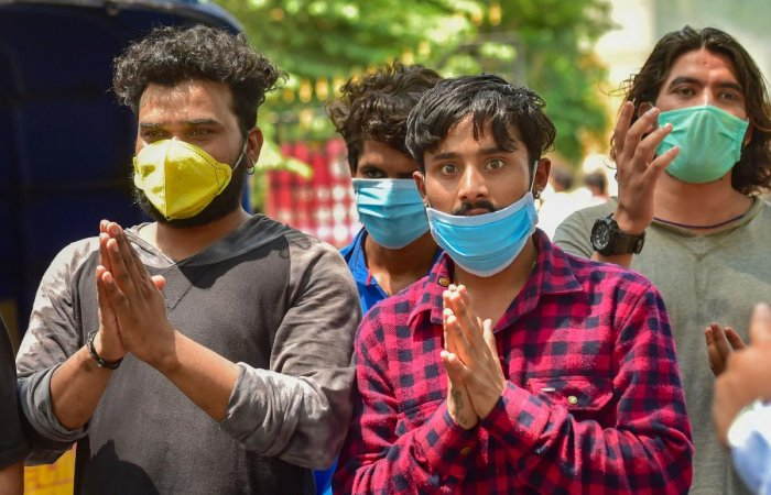 Migrant workers from Punjab, who are stranded in Bengaluru due to the lockdown, make a plea to the officials outside District Collector's office to arrange a means of transport for them on Thursday, April 30, 2020. PTI