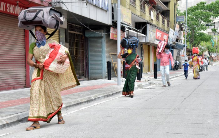 Migrant workers and their family carrying luggage and walks through KSRTC bus stop during lockdown in Bengaluru on Saturday, May 02, 2020. Photo by Janardhan B K