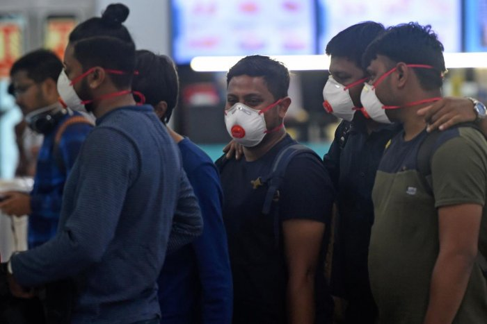 Passengers wearing facemasks amid concerns over the spread of the COVID-19 novel coronavirus, stand in a queue at a counter inside the airport in Goa. AFP