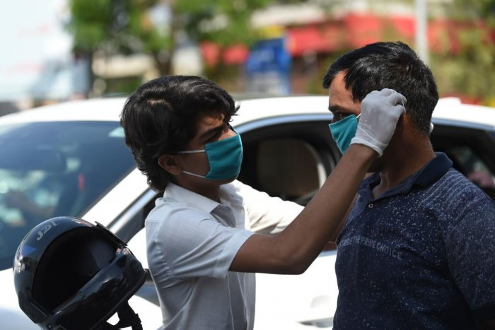 A volunteer of the Humf NGO adjusts a free facemask to a motorist during a facemaks donation campaing amid concerns over the spead of the COVID-19 coronavirus, in Ahmedabad on March 17, 2020. Credit: AFP Photo