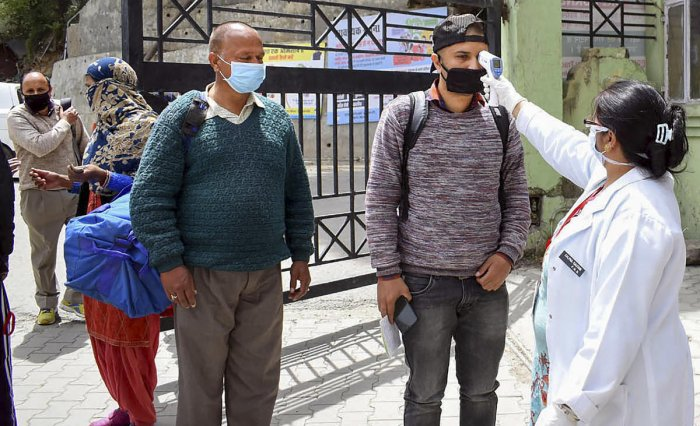 Health worker check temperature of visitors at IGMC Hospital after administration opened its OPD during the nationwide lockdown, imposed to curb the coronavirus pandemic, Shimla, Thursday, April 16, 2020. (PTI Photo)