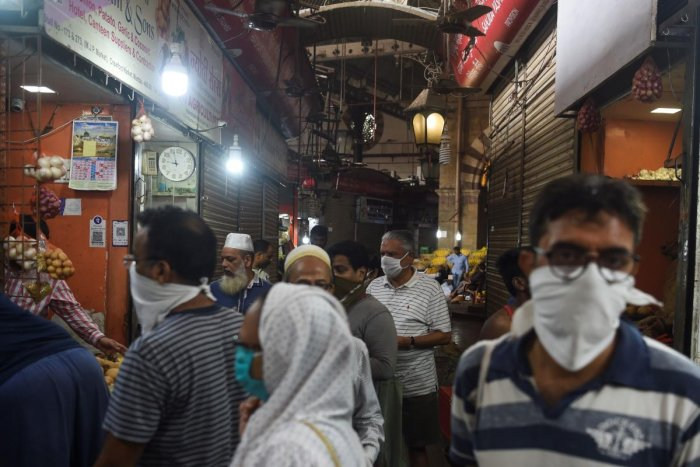 People, some wearing facemasks as a preventive measure against the COVID-19 coronavirus, shop in a local market during a government-imposed lockdown in Mumbai on March 24, 2020. Credit: AFP Photo