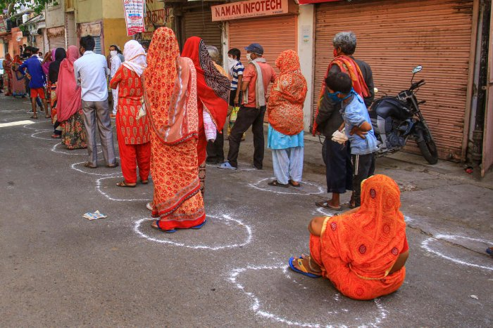 People respecting social distancing guidelines wait in queues to receive food during COVID-19 lockdown in Jaipur, Sunday, April 26, 2020. (PTI Photo)
